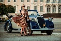 Schöne Dame mit Tasche nahe klassischem Kabriolett stockfotos