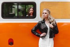 Schöne Damen, die nahe Retro- Auto stehen lizenzfreie stockfotos