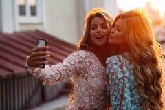 Schöne Damen, die zur Sonnenuntergangzeit gehen und zusammen Foto machen lizenzfreies stockfoto