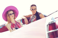 Schöne Damen mit den Sonnenbrillen, die ein Retro- Auto der Weinlese reiten Stockfotos