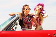 Schöne Damen mit den Sonnenbrillen, die in einem Retro- Auto der Weinlese aufwerfen Lizenzfreies Stockbild