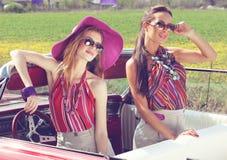 Schöne Damen mit den Sonnenbrillen, die in einem Retro- Auto der Weinlese aufwerfen Stockbild