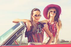 Schöne Damen mit den Sonnenbrillen, die in einem Retro- Auto der Weinlese aufwerfen Lizenzfreie Stockfotos