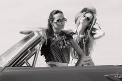 Schöne Damen mit den Sonnenbrillen, die in einem Weinleseauto in einem sonniger Tagesfrühlingssommer aufwerfen Lizenzfreie Stockbilder
