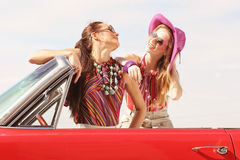 Schöne Damen mit den Sonnenbrillen, die in einem Weinleseauto in einem sonniger Tagesfrühlingssommer aufwerfen Stockfotografie