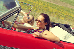 Schöne Damen mit den Sonnenbrillen, die in einem Weinleseauto in einem sonniger Tagesfrühlingssommer aufwerfen Lizenzfreies Stockfoto
