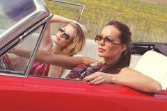 Schöne Damen mit den Sonnenbrillen, die in einem Weinleseauto in einem sonniger Tagesfrühlingssommer aufwerfen Lizenzfreies Stockbild