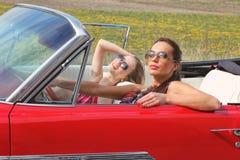 Schöne Damen mit den Sonnenbrillen, die in einem Weinleseauto in einem sonniger Tagesfrühlingssommer aufwerfen Stockfoto