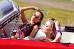 Schöne Damen mit den Sonnenbrillen, die in einem Weinleseauto in einem sonniger Tagesfrühlingssommer aufwerfen Lizenzfreie Stockfotos