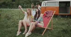 Schöne Damen am Picknick, welches die selfies sitzen auf den Picknickstühlen, Hintergrundgruppe von Freunden aufwendend nimmt stock video
