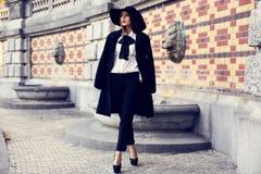 Schöne damenhafte Frau im Mantel und in geglaubtem Hut, die am Park aufwerfen lizenzfreie stockbilder
