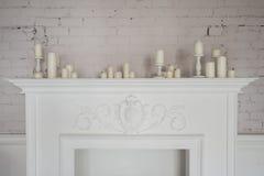Schöne Dekorationen des Kamins mit Kerzen im bequemen Wohnzimmer Stockbilder
