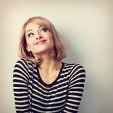 Schöne denkende blonde junge Frau des Spaßes in der Strickjacke, die oben schaut Stockfotos