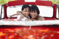 Schöne Doppelschwestern, die im Cabrioletauto umarmen Lizenzfreie Stockbilder