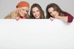 Schöne drei weibliche Freunde mit leerem Vorstand Lizenzfreie Stockfotos