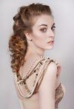 Schöne dunkle Blondine in einem Gold und in einer Perlenhalskette Stockfoto