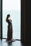 Schöne durchdachte Frau mit dem langen Haar, das in gestrickter Bettdecke steht stockfotos