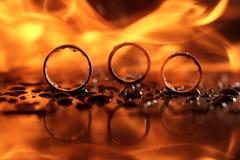 Schöne Eheringe auf Feuer mit Reflexion und im Wasser lizenzfreies stockbild