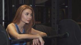 Schöne Eignungsfrau, die zur Kamera sich lehnt auf einem Barbell an der Turnhalle lächelt stock video footage