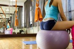 Schöne Eignungsfrau mit dem getonten auf dem Eignungsball sitzenden und tuenden Körper trainiert Stockbilder