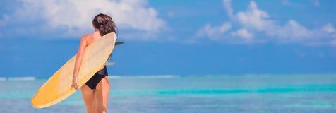 Schöne Eignungssurferfrau, die während der Sommerferien surft lizenzfreie stockfotografie