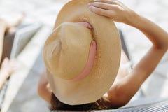Schöne ein Sonnenbad nehmende Frau, die Hut hält Stockfoto