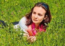 Schöne einsame Frau, die in das Gras wartet Stockbild