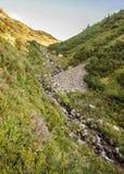 Schöne Einstellung des Weges Gebirgsumgeben durch enorme Hügel Stockfotografie