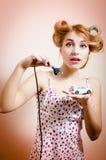 Schöne elegante blonde junge Pinupfrau, die für aufladendes vorbildliches Spielzeugauto mit der elektrischen Schnur betrachtet Ka Stockfoto