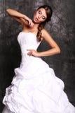 Schöne elegante Braut mit dem dunklen Haar, das am Studio aufwirft Lizenzfreies Stockbild