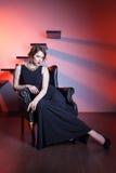 Schöne elegante Frau, die auf einem Lehnsessel sitzt Lizenzfreie Stockfotos