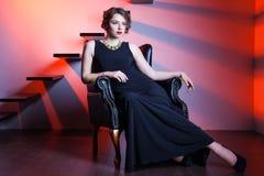 Schöne elegante Frau, die auf einem Lehnsessel sitzt Stockfotografie