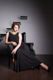 Schöne elegante Frau, die auf einem Lehnsessel sitzt Stockfotos