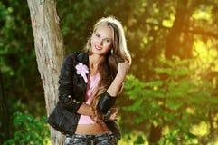 Schöne elegante Frau, die in einem Park steht Stockfotografie
