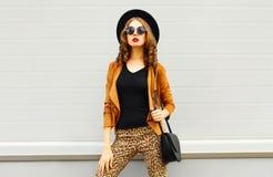 Schöne elegante Frau, die einen Retro- eleganten Hut, eine Sonnenbrille, eine braune Jacke und eine schwarze Handtasche trägt lizenzfreies stockfoto