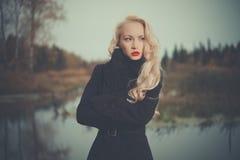 Schöne elegante Frau in einem schwarzen Mantel lizenzfreies stockfoto