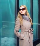 Schöne elegante Frau kleidete einen Mantel und Sonnenbrille draußen stockbild