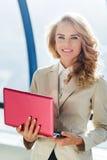Schöne elegante Geschäftsdame mit dem roten Laptop, der Kamera betrachtet lizenzfreie stockfotografie