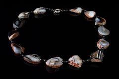 Schöne, elegante Halskette des schwarzen Achatsteins auf einem schwarzen Hintergrund Lizenzfreie Stockbilder