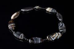 Schöne, elegante Halskette des schwarzen Achatsteins auf einem schwarzen Hintergrund Lizenzfreie Stockfotos