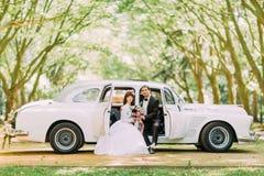Schöne emotionale blonde Braut mit Blumenstrauß von den weißen Rosen, die im Frühjahr Park aufwerfen Stockbilder