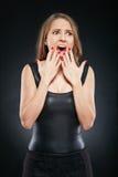 Schöne emotionale Frau über dunklem Hintergrund Stockfotografie