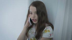 Schöne emotionale Unterhaltung des kleinen Mädchens am intelligenten Telefon stock video footage