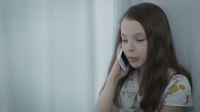 Schöne emotionale Unterhaltung des kleinen Mädchens am intelligenten Telefon stock video