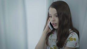 Schöne emotionale Unterhaltung des kleinen Mädchens am intelligenten Telefon durch Fenster stock video