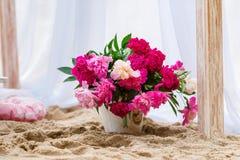 Schöne, empfindliche Hochzeitsdekorationen mit Kerzen und frische Blumen auf dem Strand Stockfoto