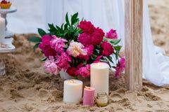 Schöne, empfindliche Hochzeitsdekorationen mit Kerzen und frische Blumen auf dem Strand Lizenzfreies Stockfoto