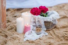 Schöne, empfindliche Hochzeitsdekorationen mit Kerzen und frische Blumen auf dem Strand Stockbild