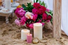 Schöne, empfindliche Hochzeitsdekorationen mit Kerzen und frische Blumen auf dem Strand Lizenzfreie Stockbilder
