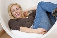 Schöne entspannte Frau, die in einem Luftblasen-Stuhl lacht Lizenzfreies Stockbild